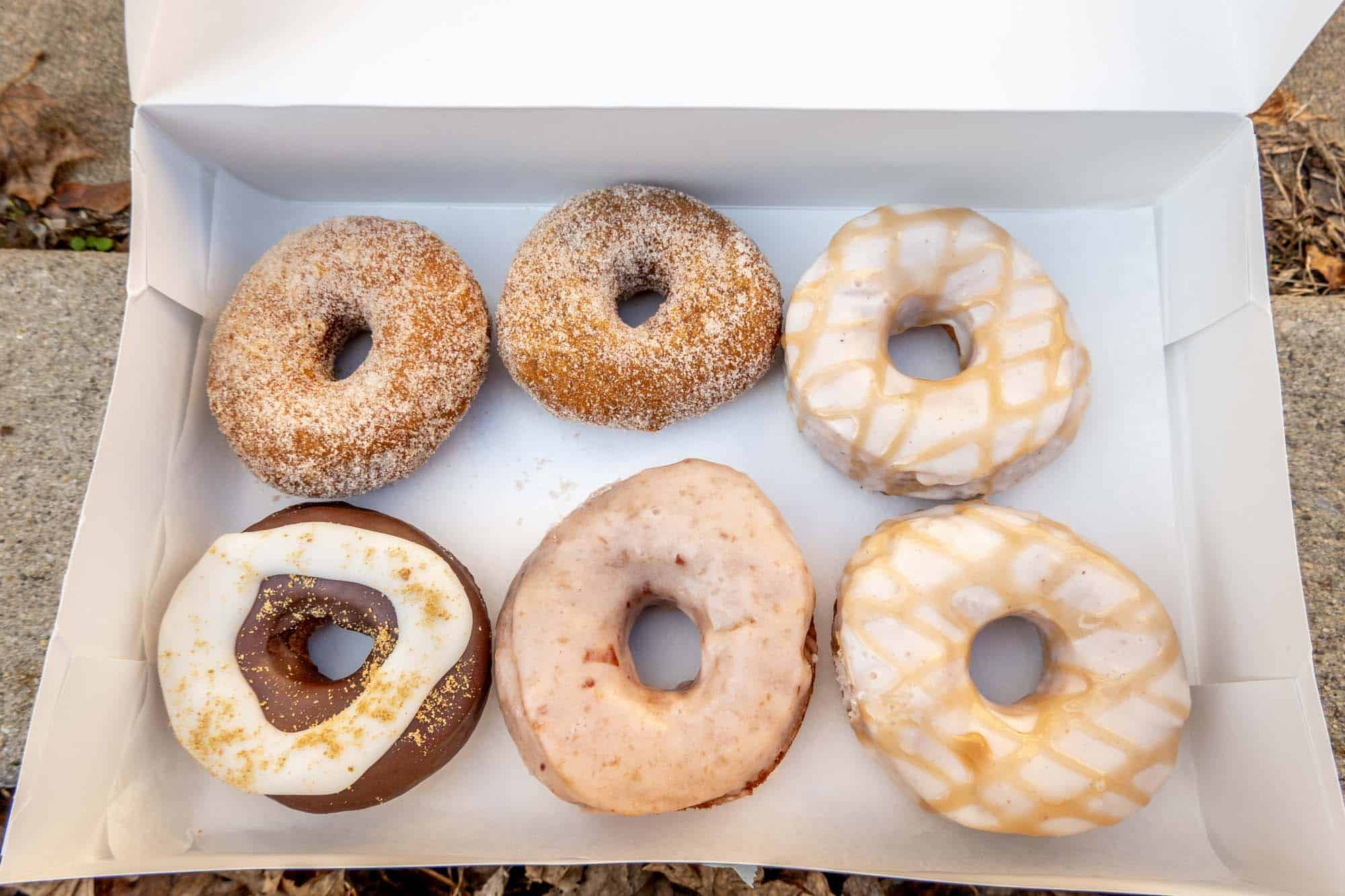 Six donuts topped with sugar and icing in a box