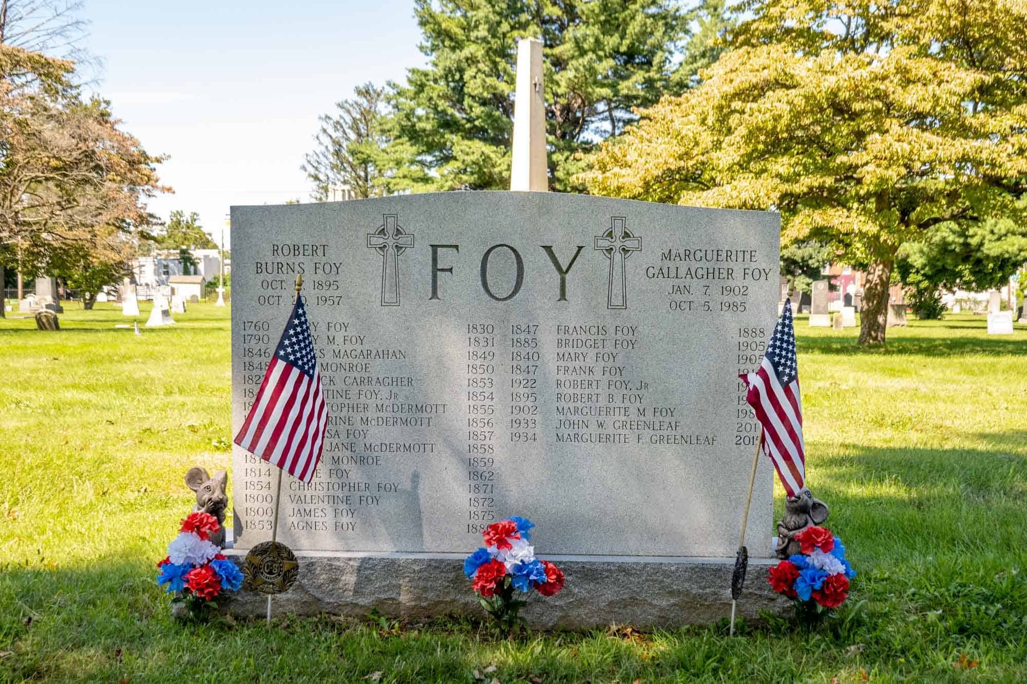 Large tombstone with many family names on it, with American flags and flowers