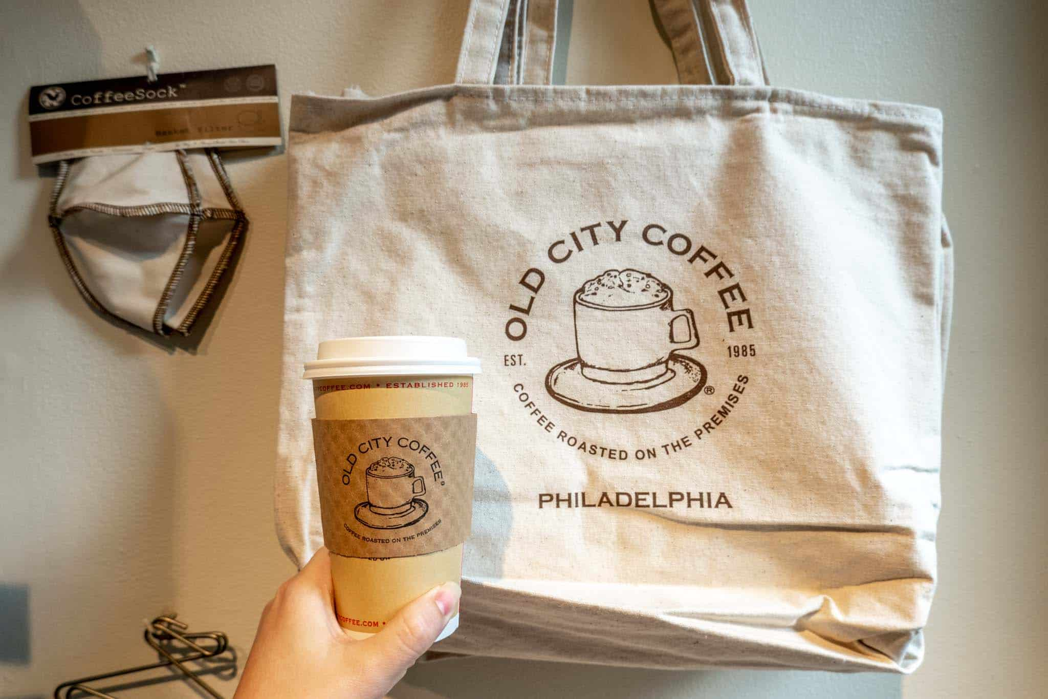 """Coffee cup beside a bag labeled """"Old City Coffee"""""""