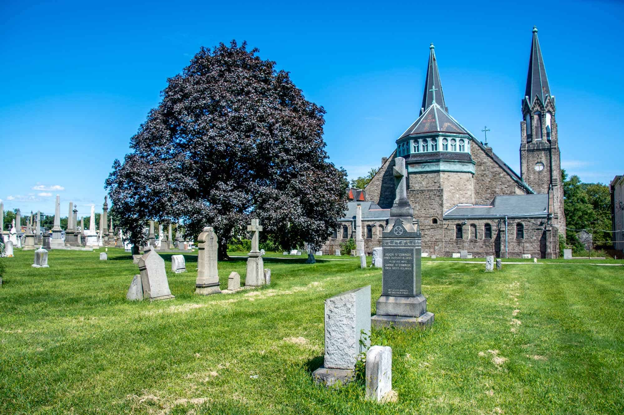Tombstones in cemetery with church with twin spires beyond