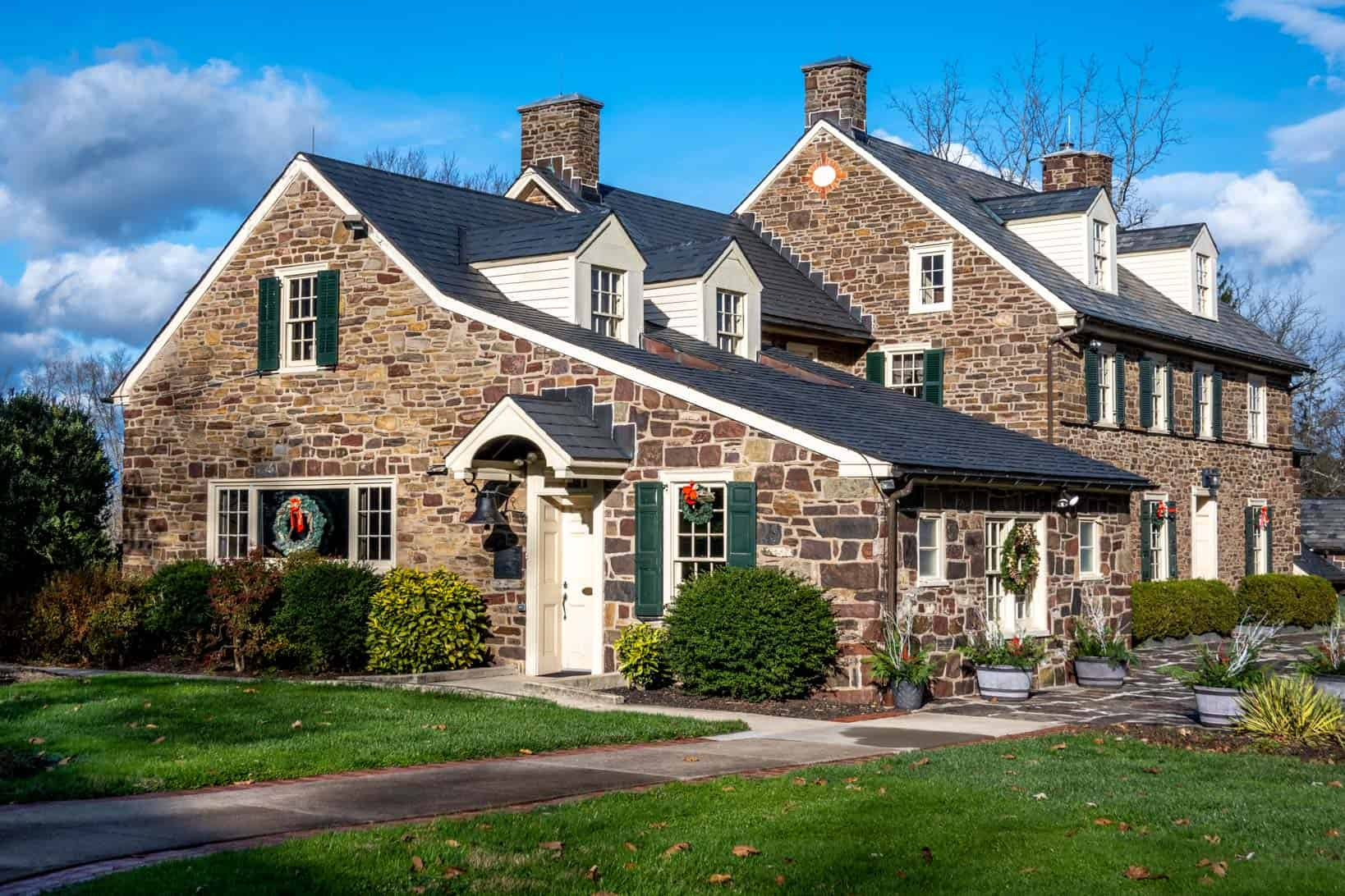 Large stone house with Christmas wreaths on the windows