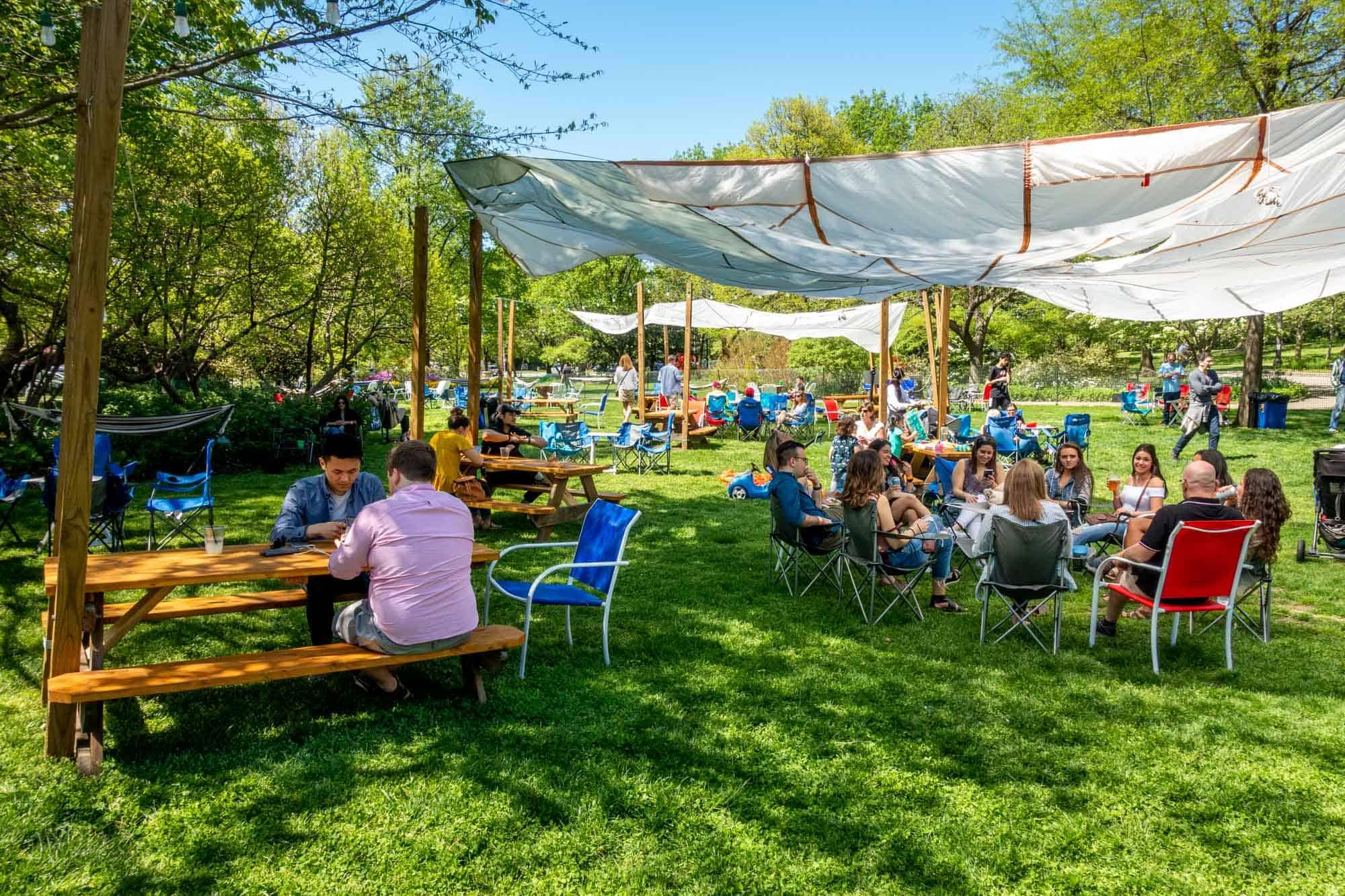 People gathering in outdoor beer garden in park
