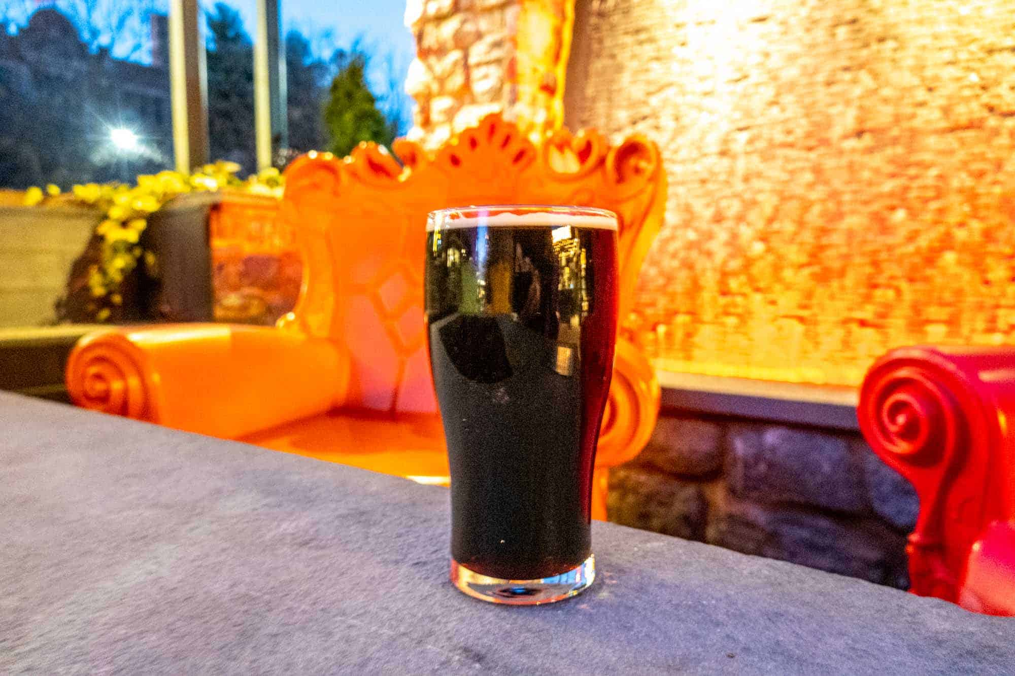 Pint of dark beer in front of funky orange and red chairs