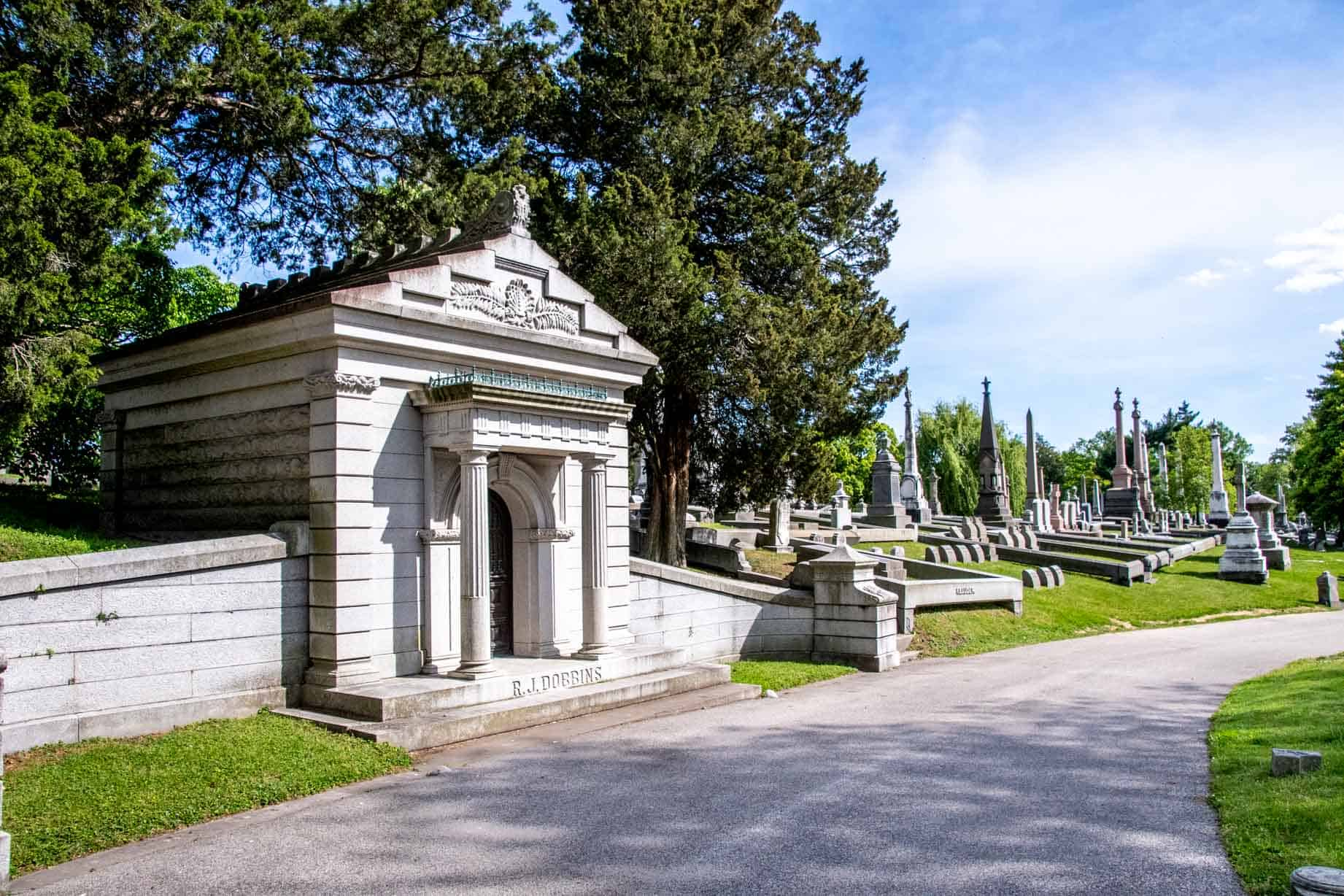 Gray mausoleum with columns next to a road in Laurel Hill Cemetery