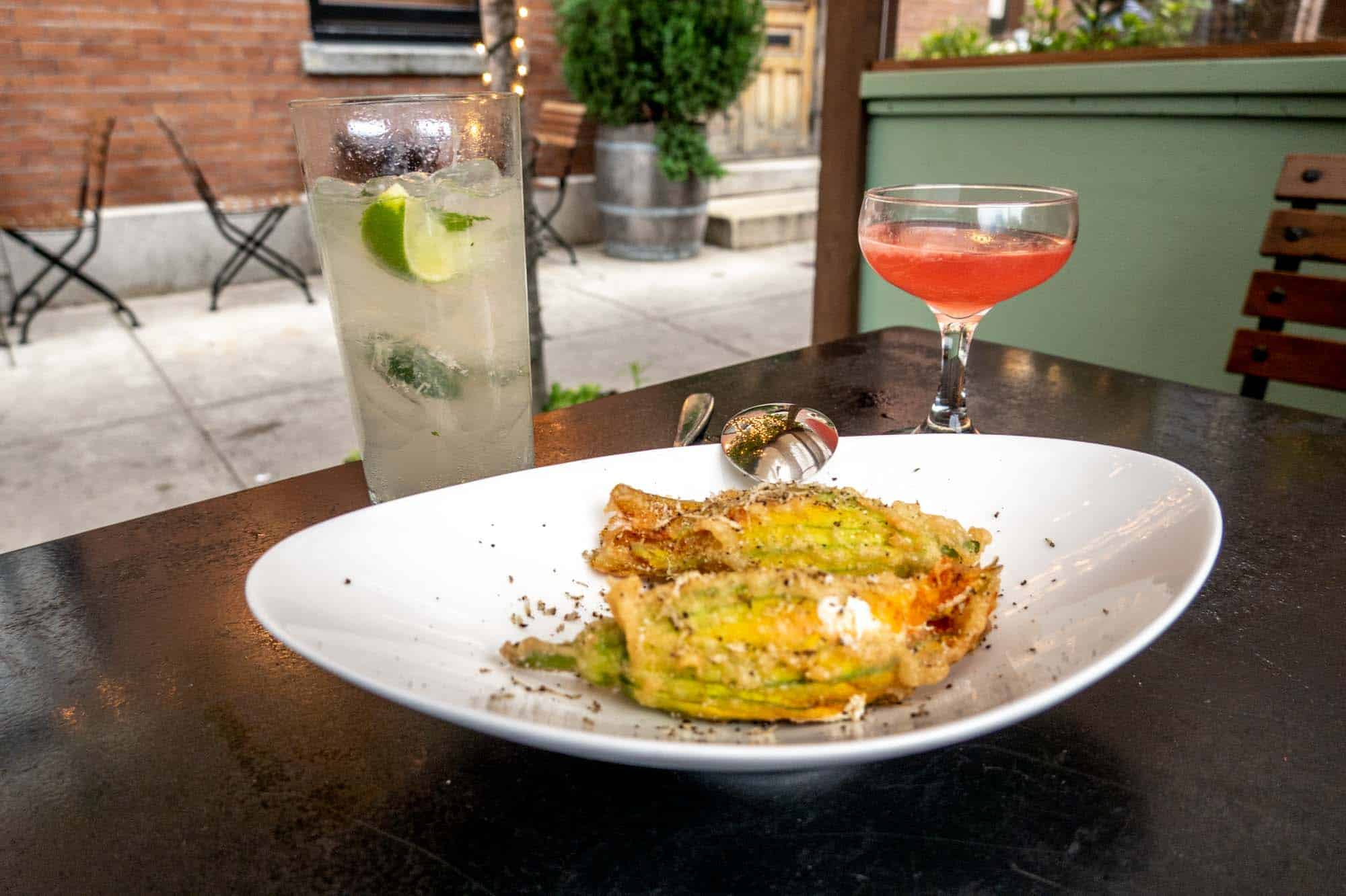 Fried zucchini blossoms on a plate beside two cocktails