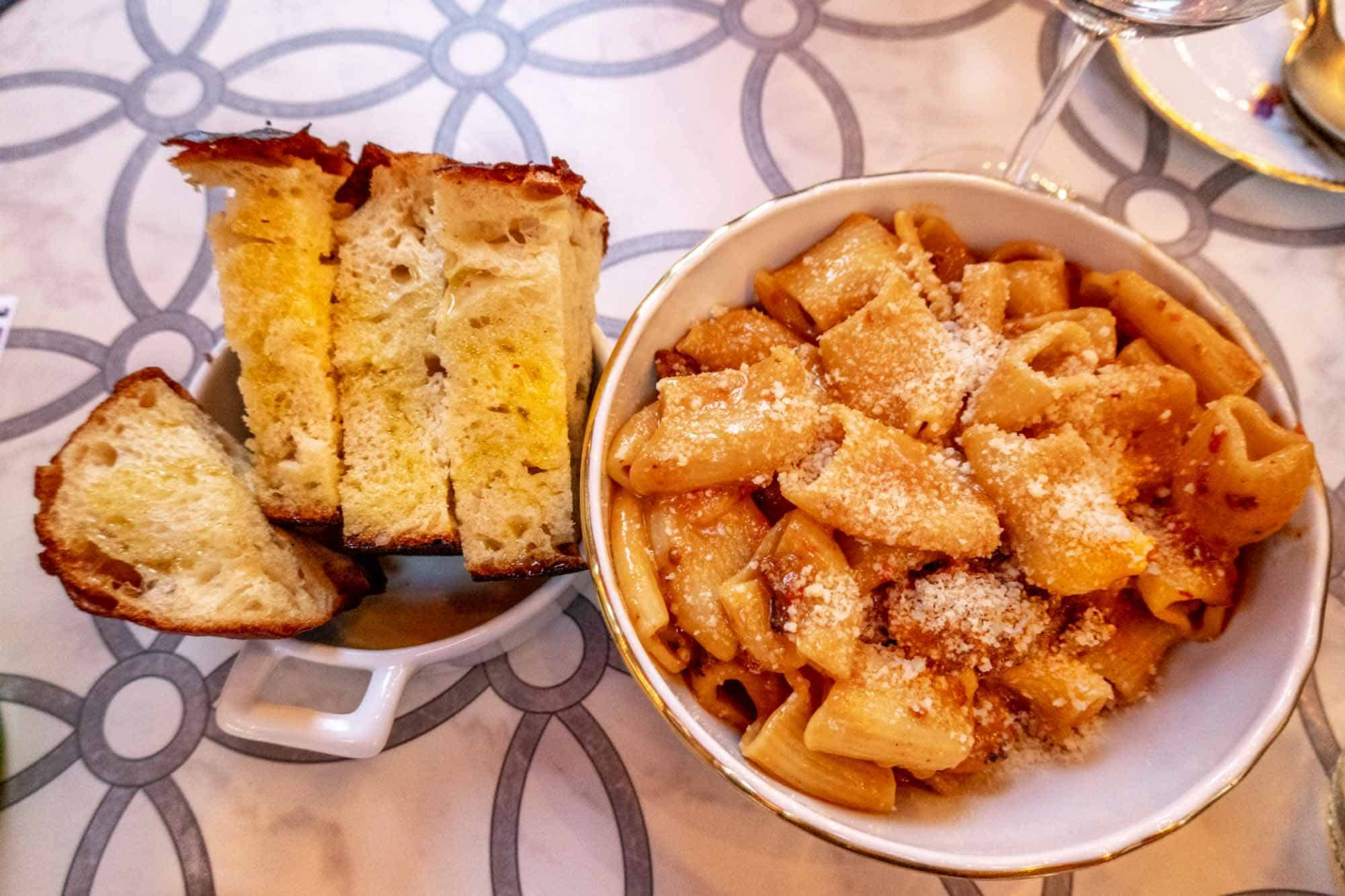 Bowl of rigatoni pasta, plus side of focaccia bread