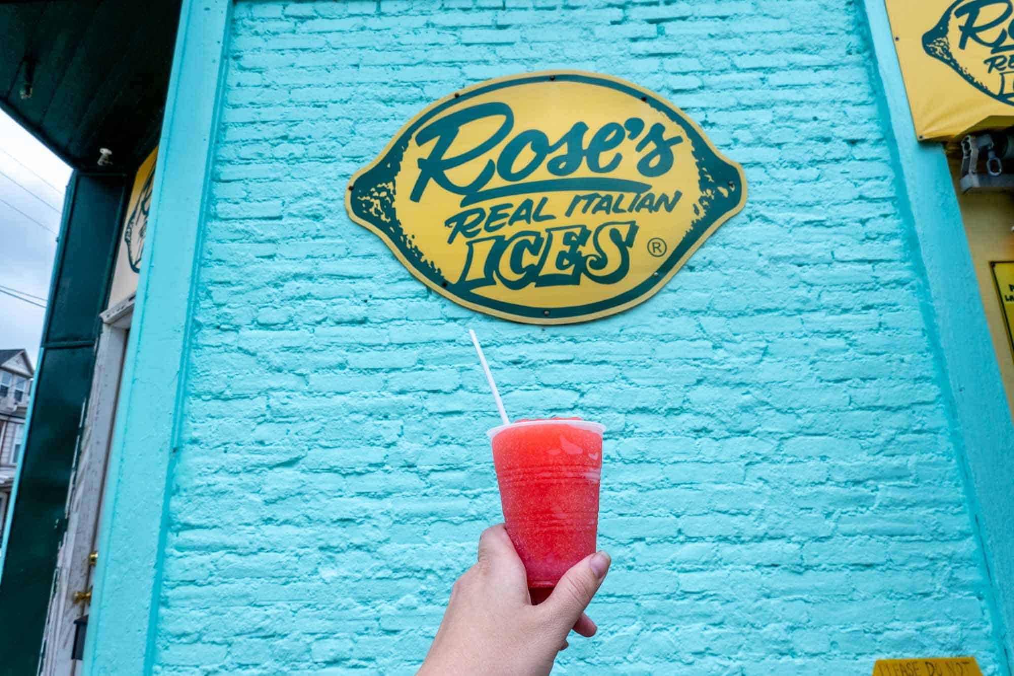 Cup filled with cherry ice in front of sign for Rose's Real Italian Ices