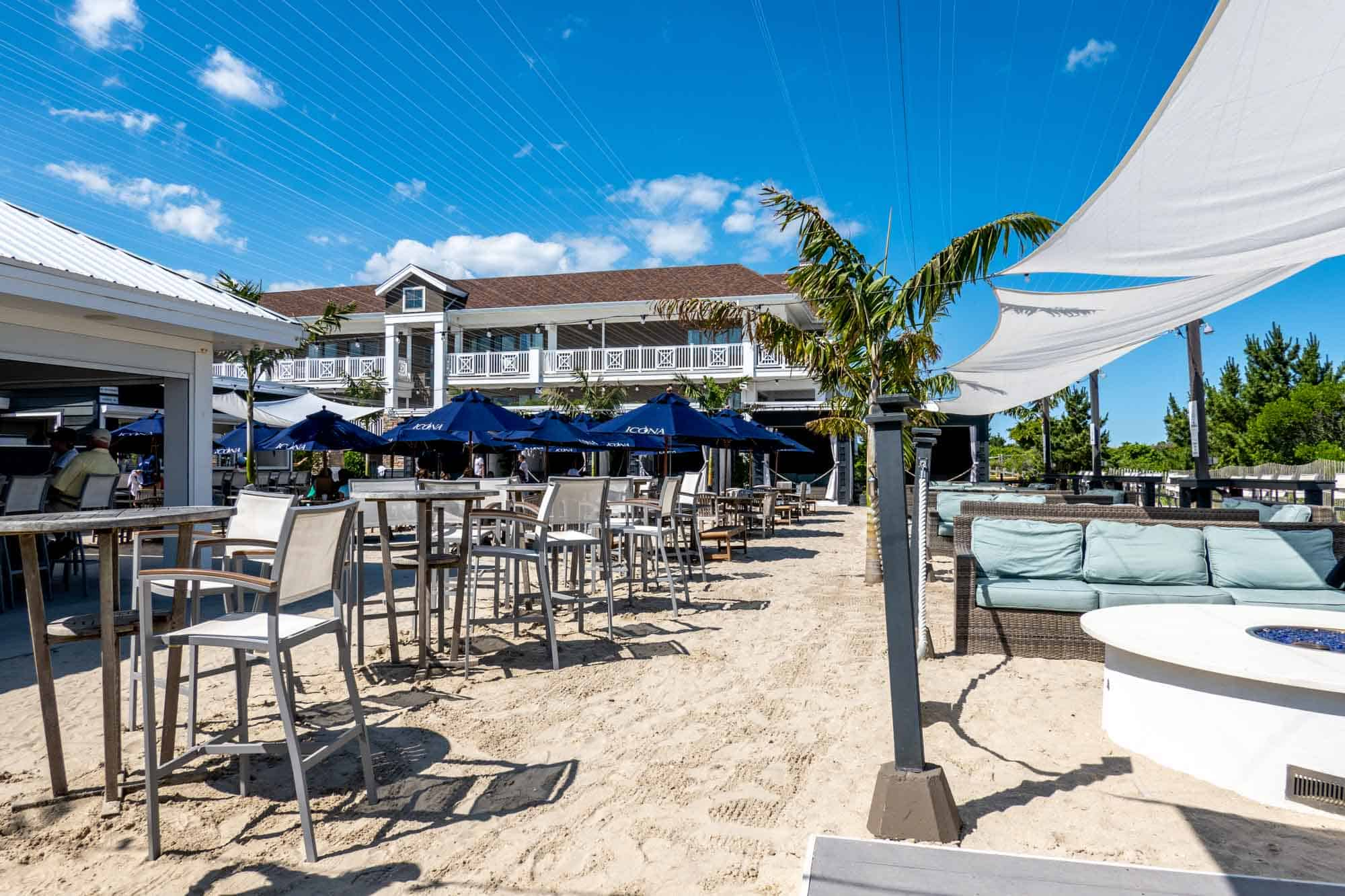 Couches, fire pits and tables at a beach bar