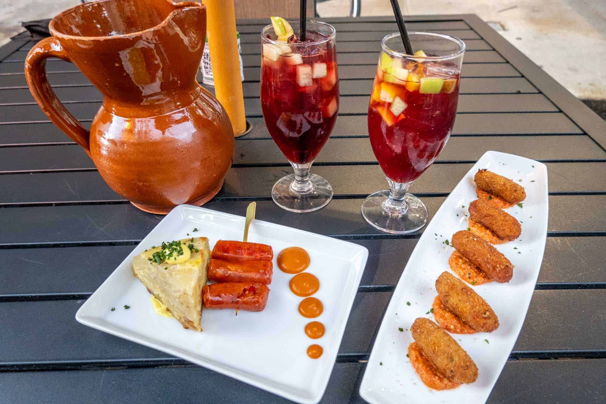 Spanish tortilla and Croquetas on plates with a drink