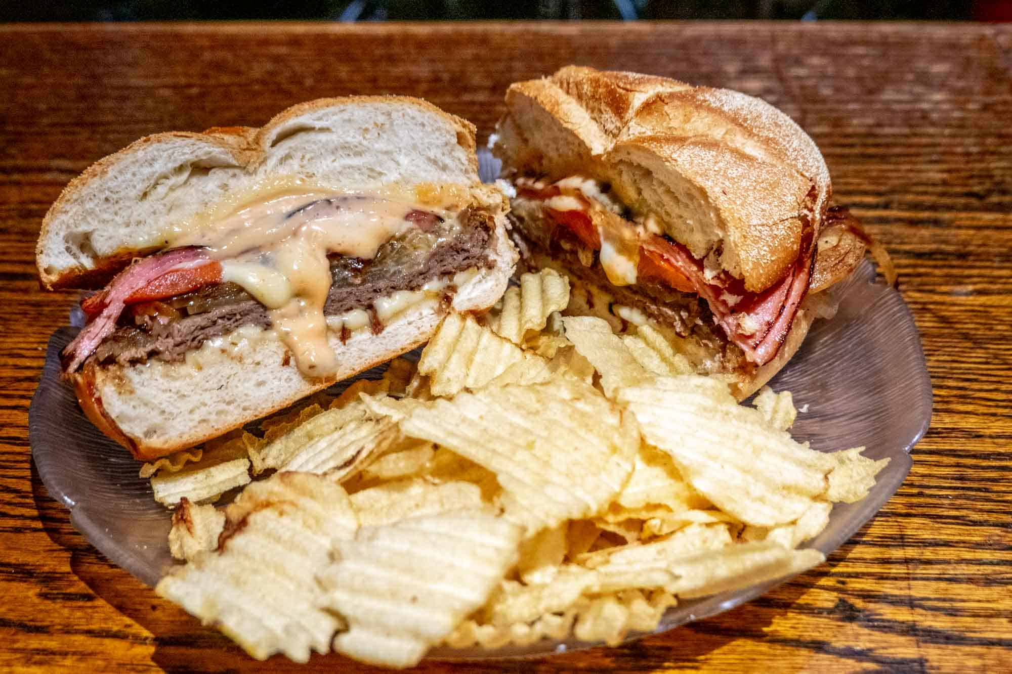Sandwich with roast beef and orange sauce on a round roll on a plate with potato chips