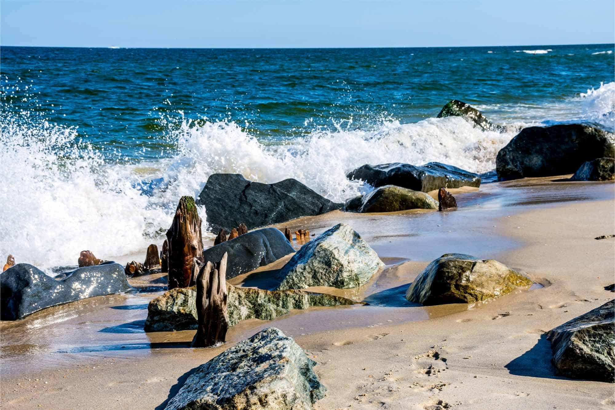 Waves crashing on beach with rocks