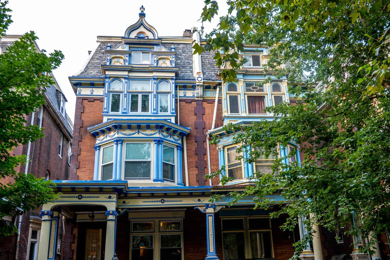 Brick Queen Anne style twin homes with blue accents