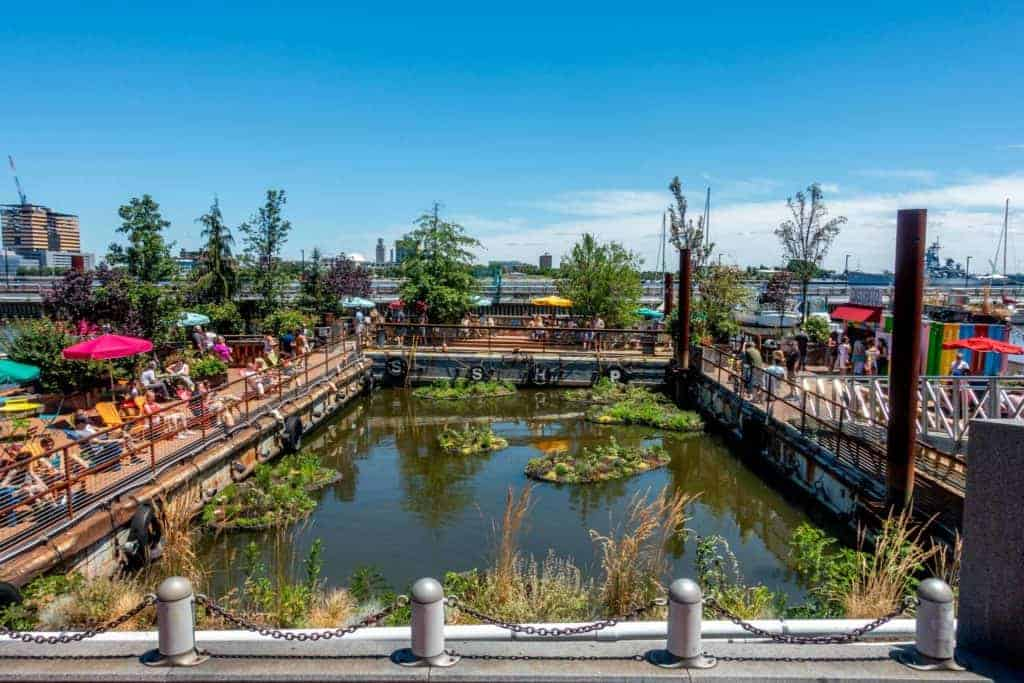Chairs, tables, and people on colorful floating platforms at Spruce Street Harbor Park