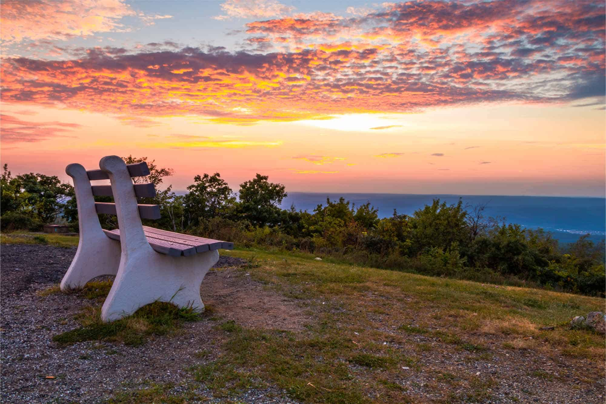 Park bench at sunset on mountain