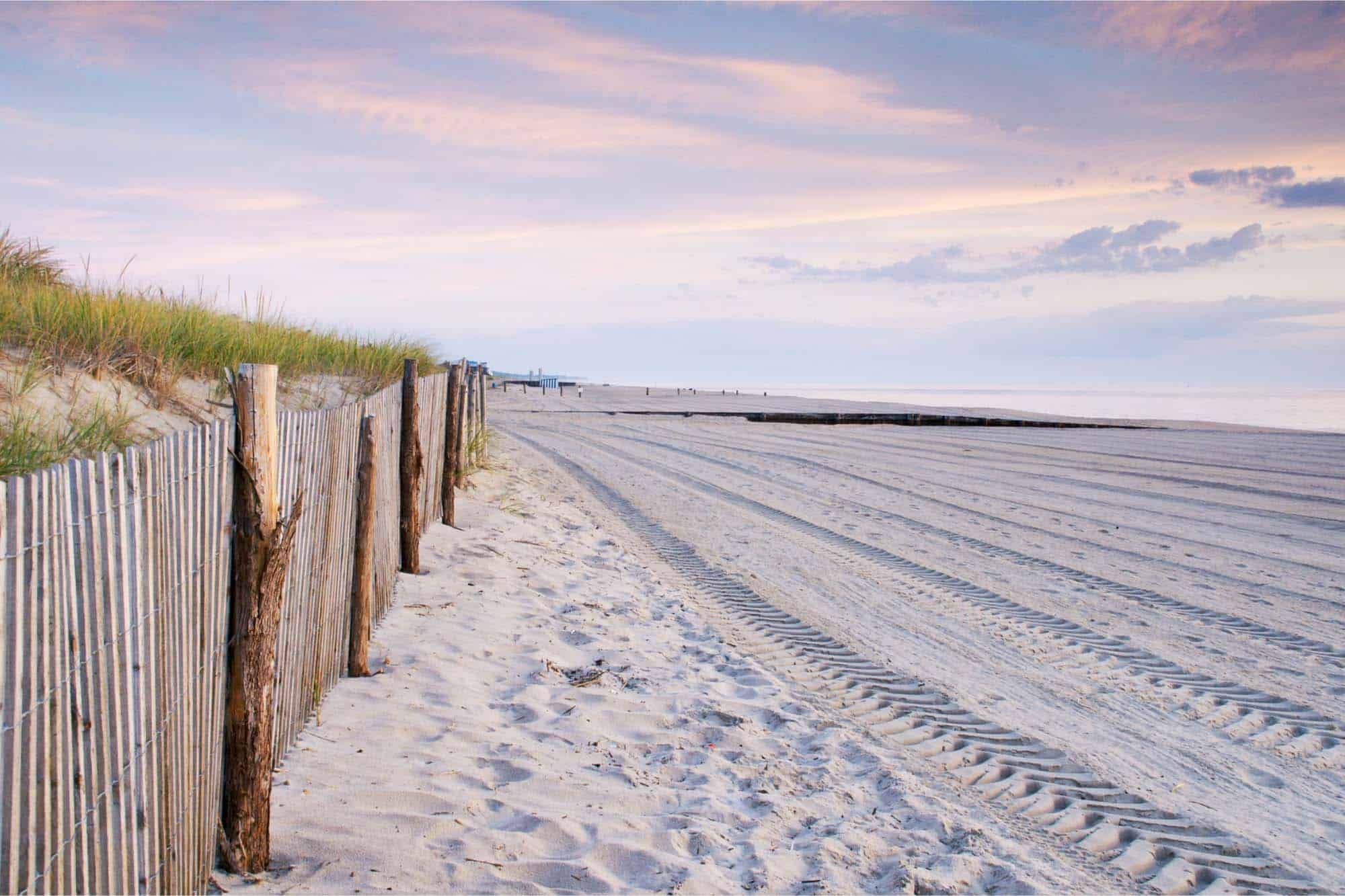 Fence and beach at sunset