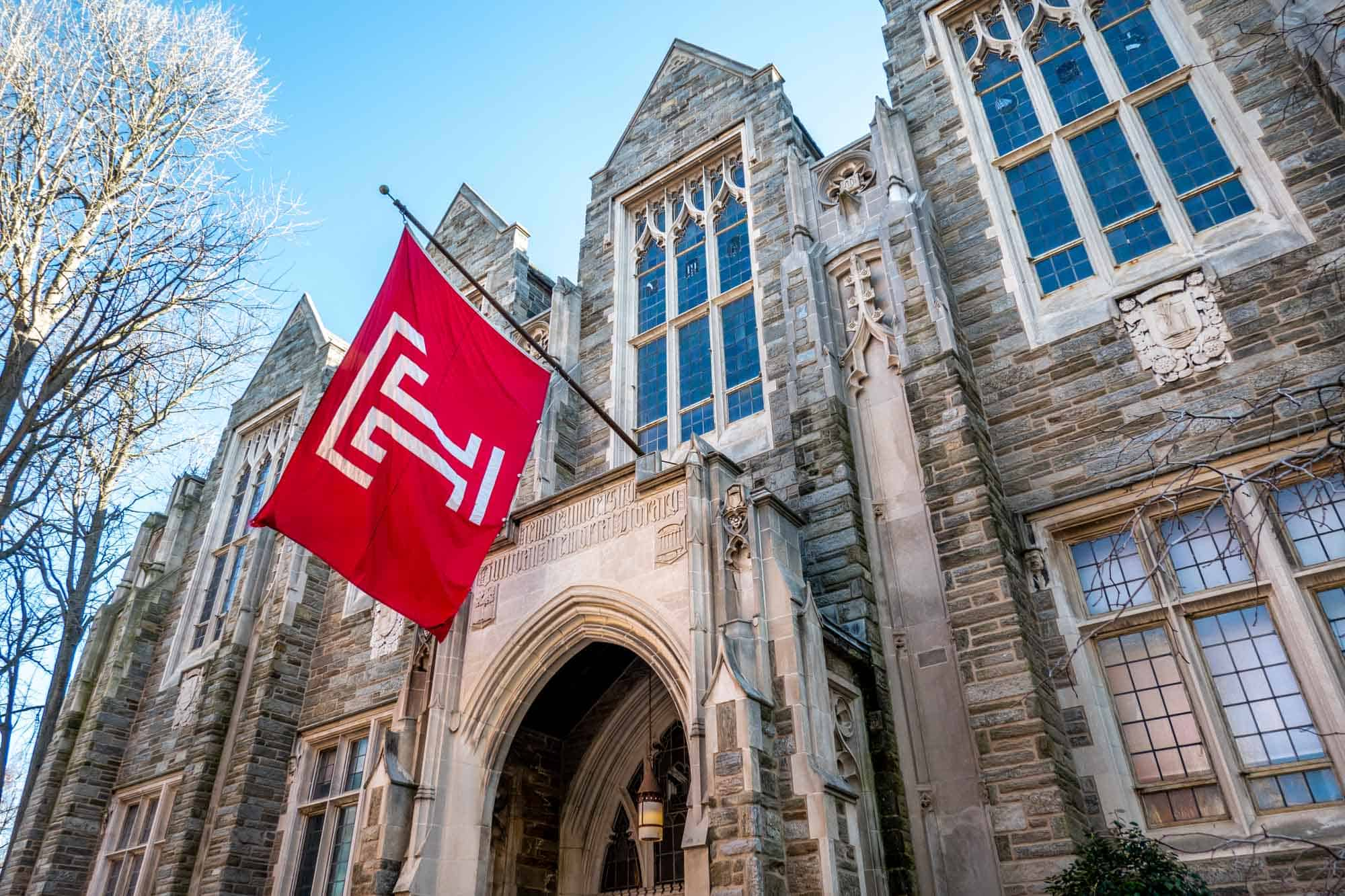 Red Temple University flag in front of building
