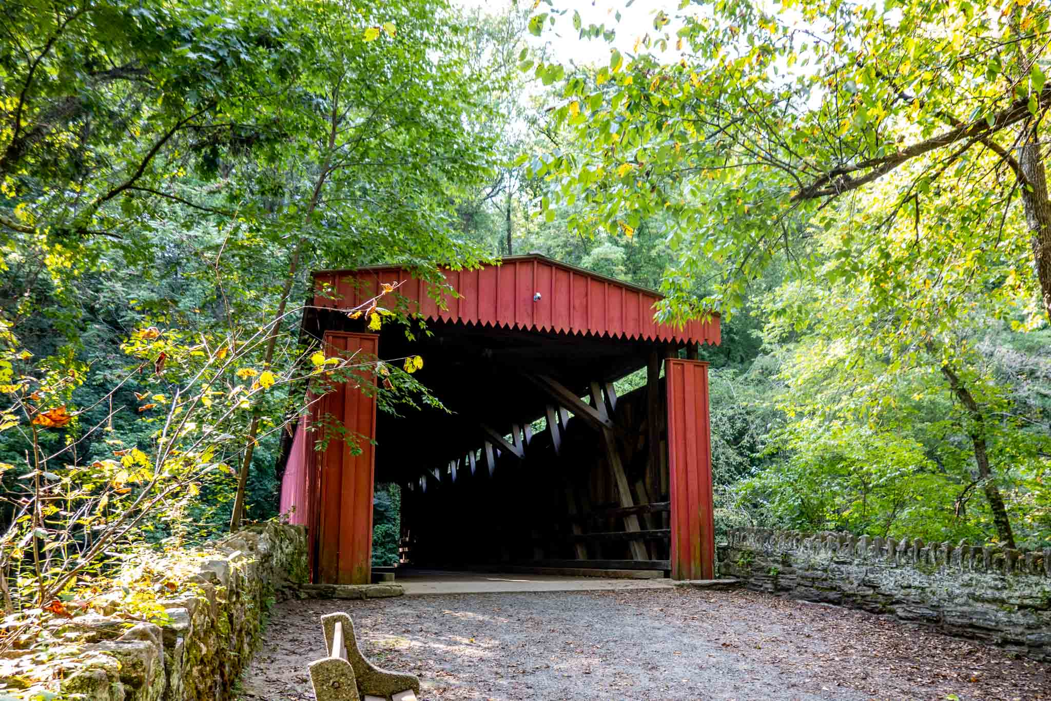 Red covered bridge surrounded by trees