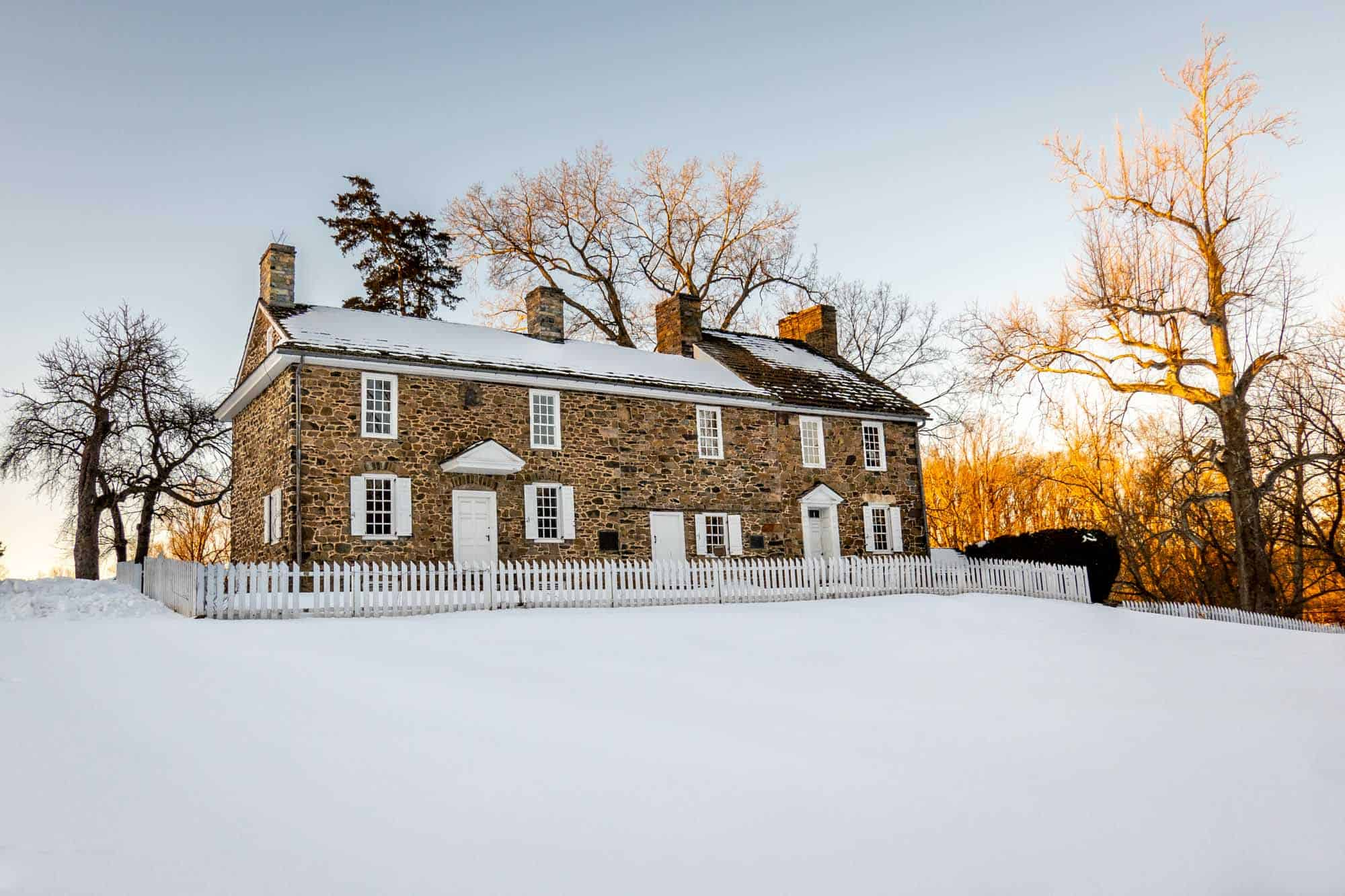 Exterior of a colonial stone building on a snowy day