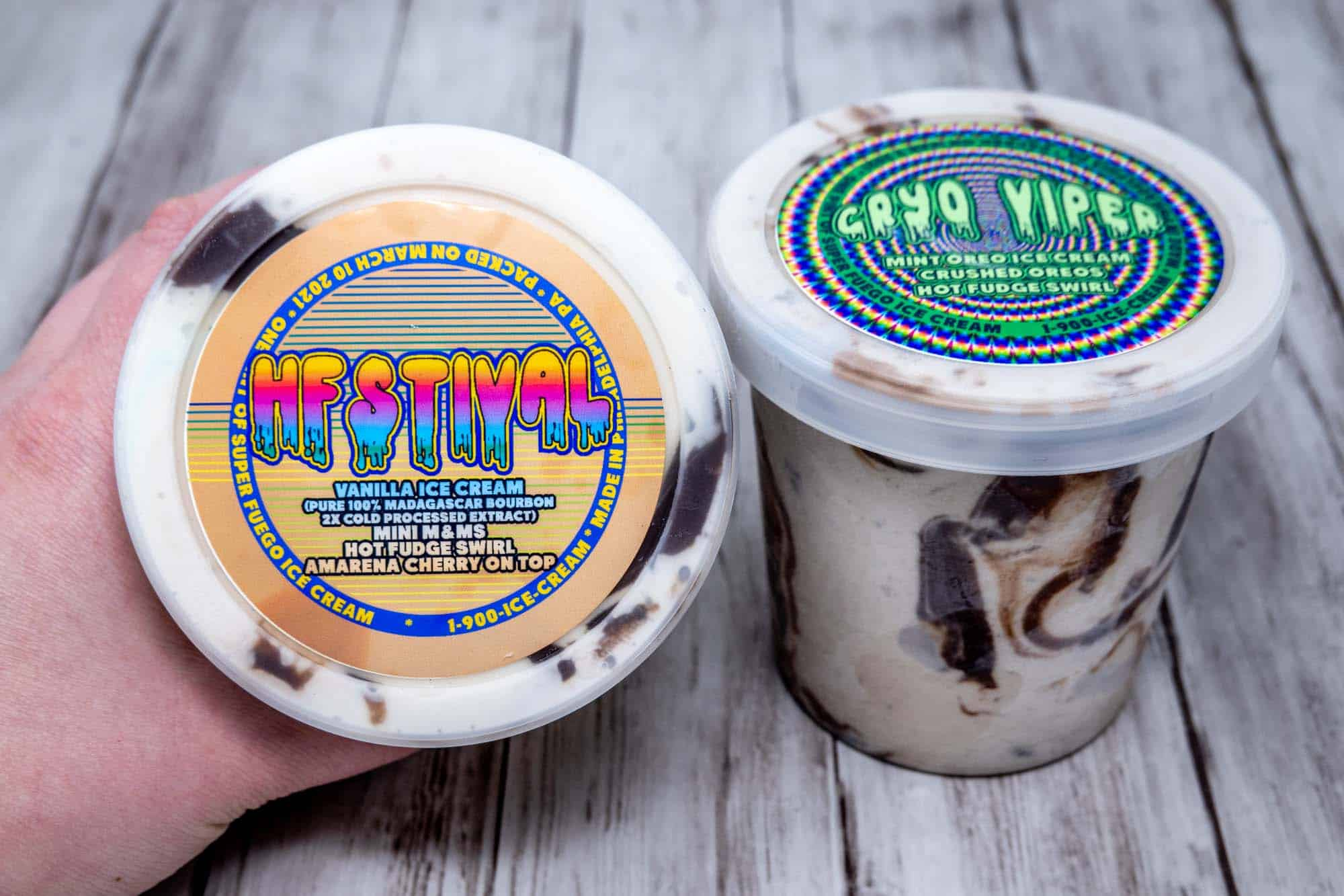 Two clear plastic pints of ice cream with chocolate swirls topped with colorful labels