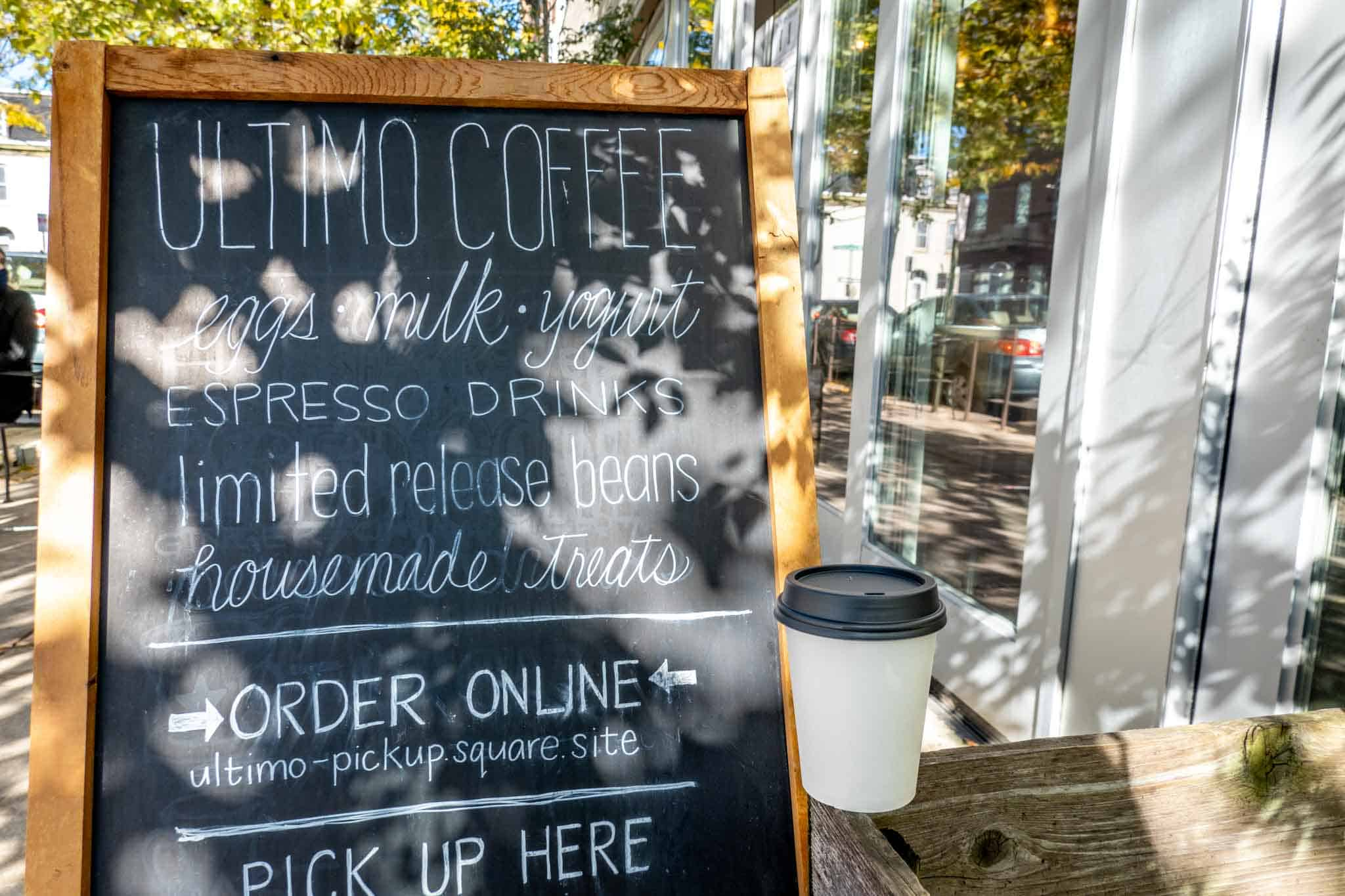 """Cup beside a sign: """"Ultimo Coffee: eggs, milk, yogurt, espresso drinks, limited release beans, homemade treats"""""""