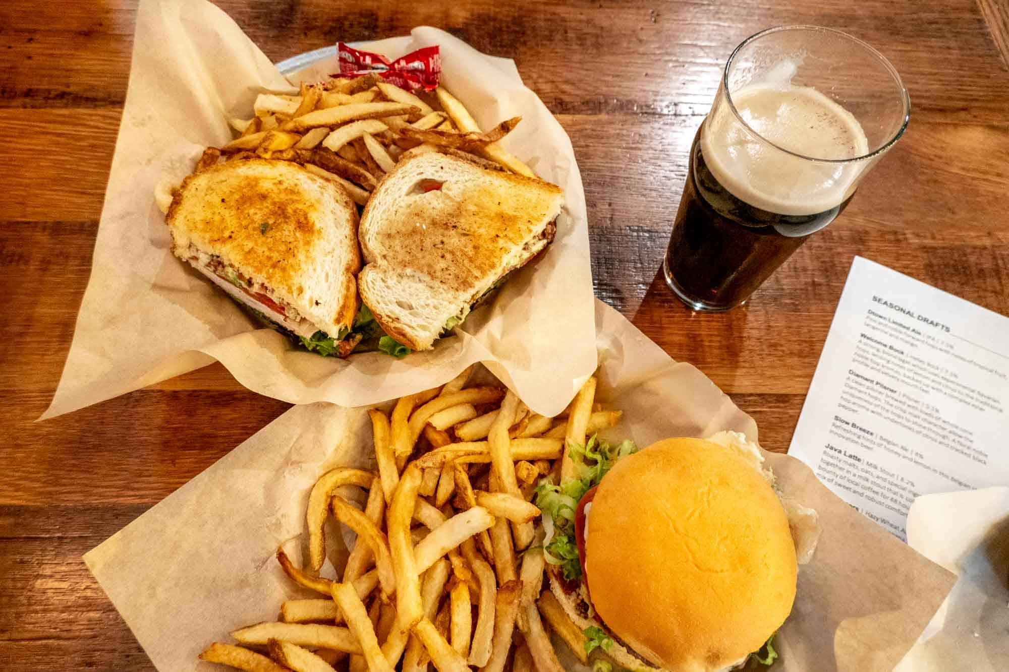 Two sandwiches with french fries and a beer on a table