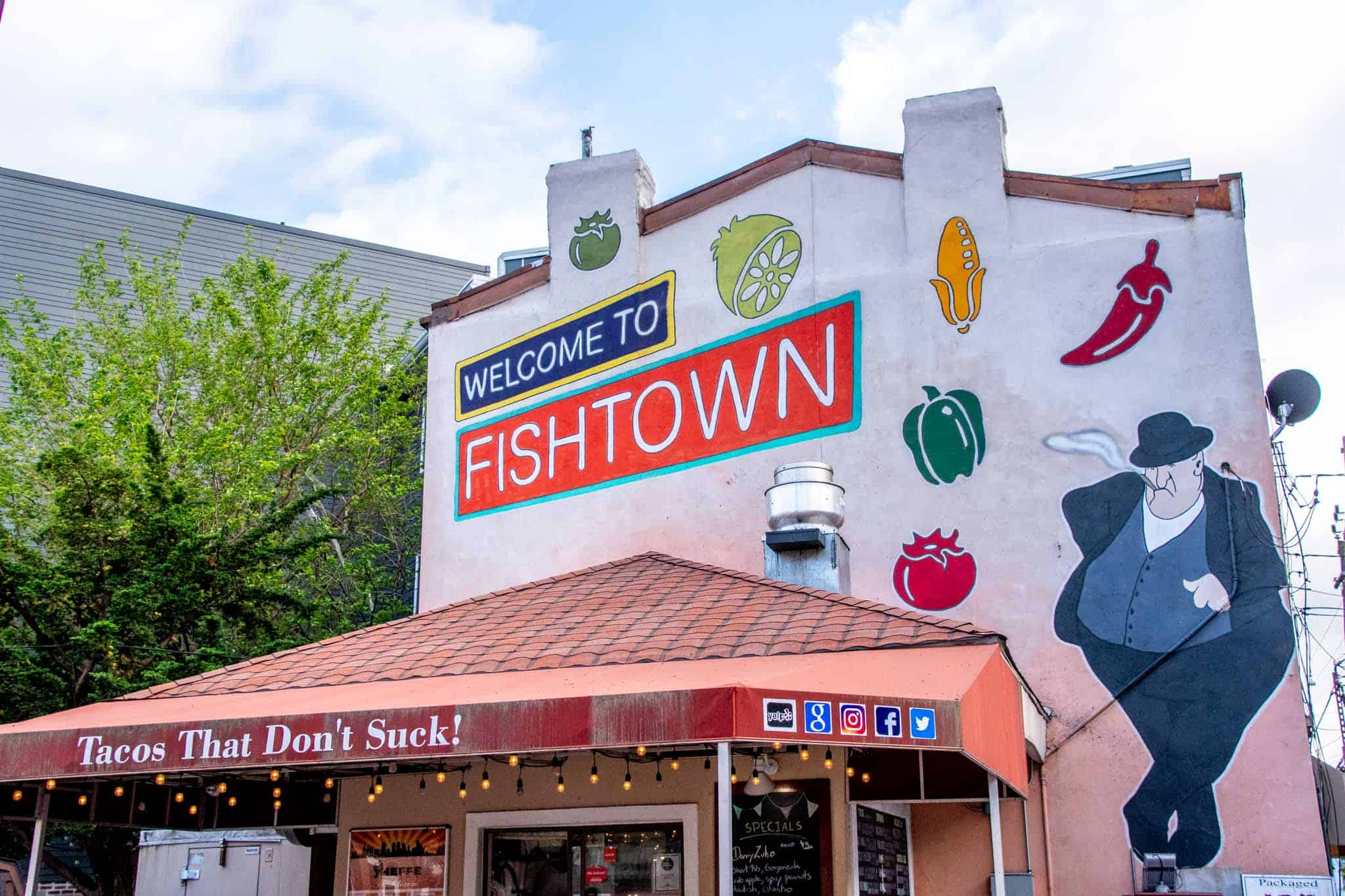 Welcome to Fishtown mural, including cartoon-style fruits and vegetable and a man with a cane
