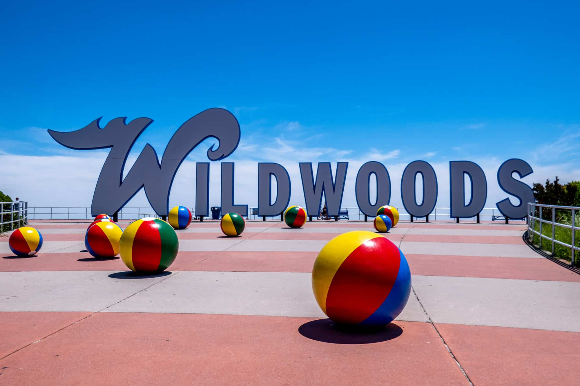"""The """"Wildwoods"""" sign with colorful beach balls on the sidewalk"""