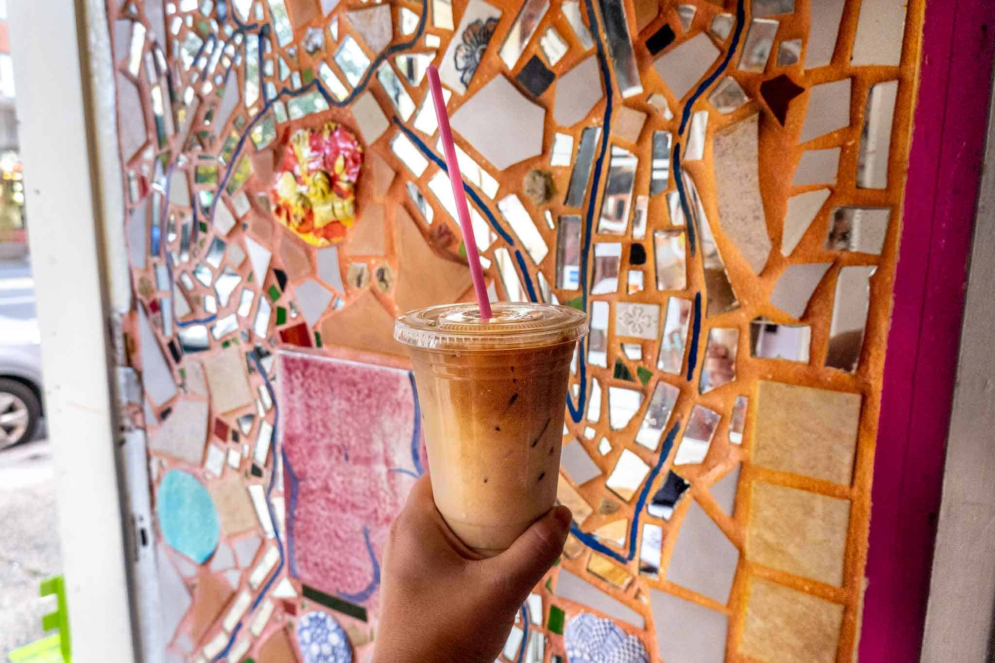 Hand holding a cup in front of a mosaic wall