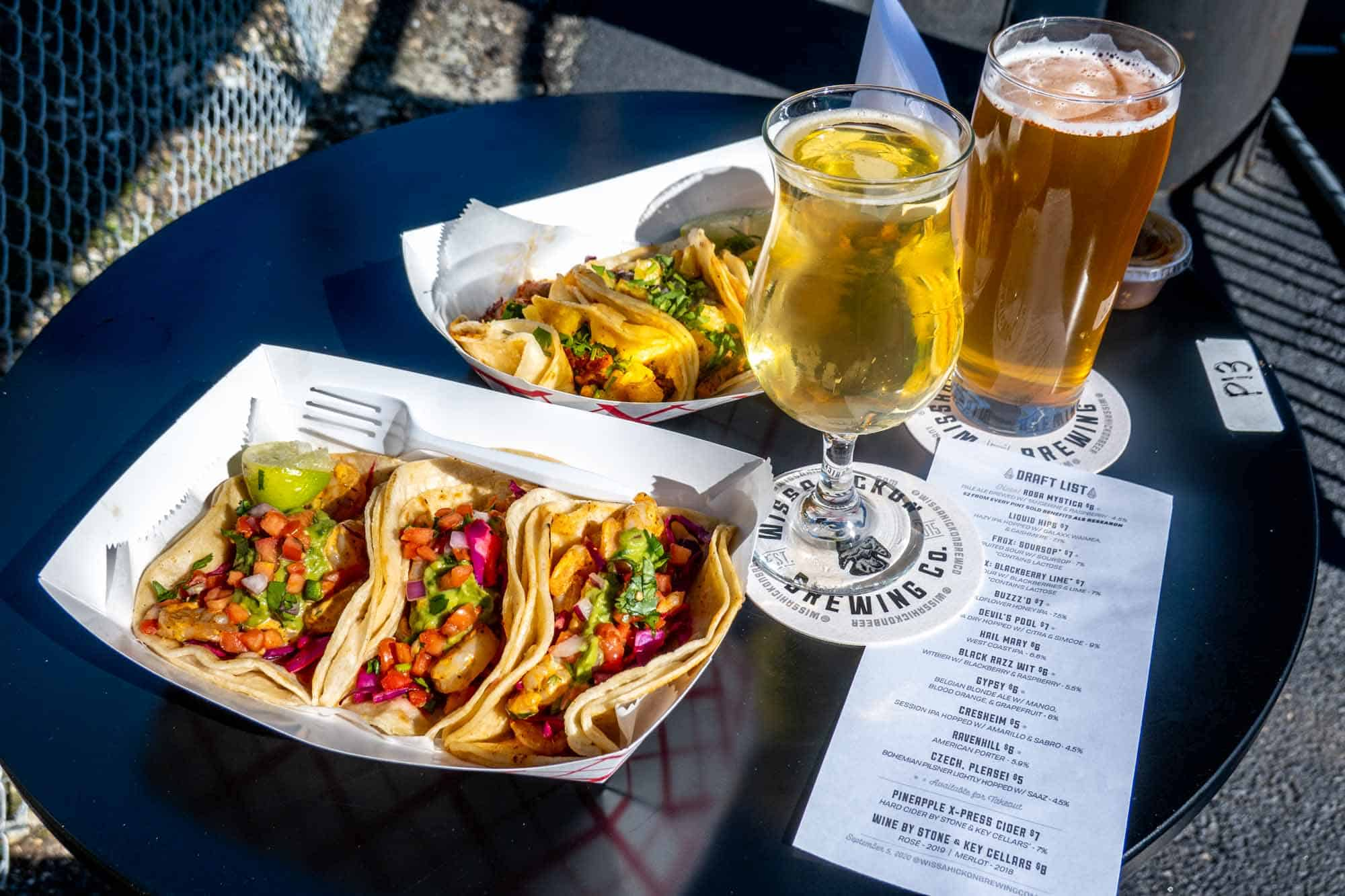 Trays of tacos on a table with two beers