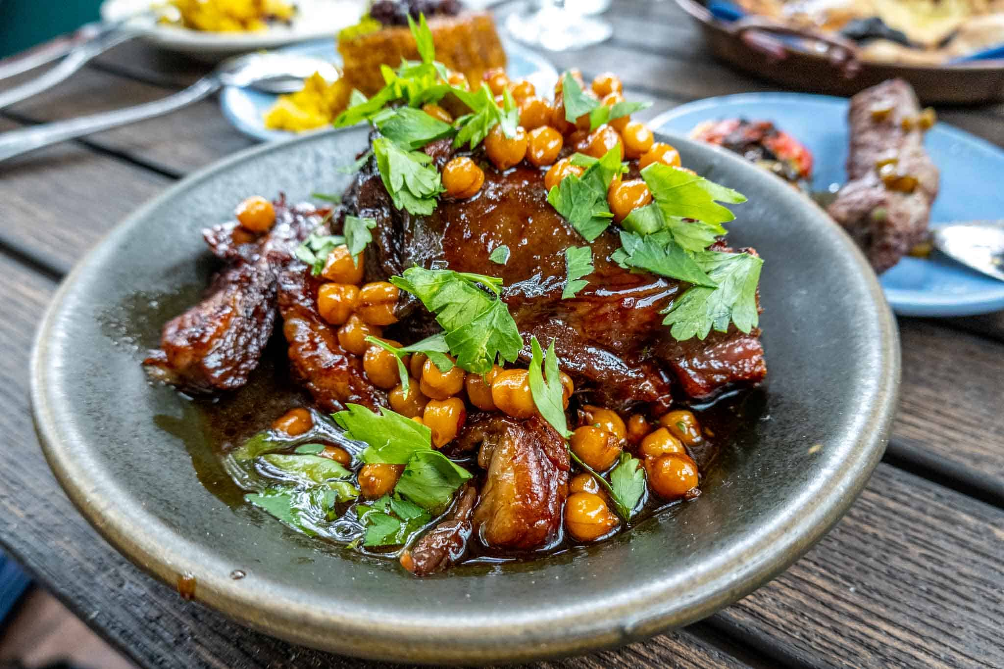 Roasted lamb topped with chickpeas and cilantro in a bowl