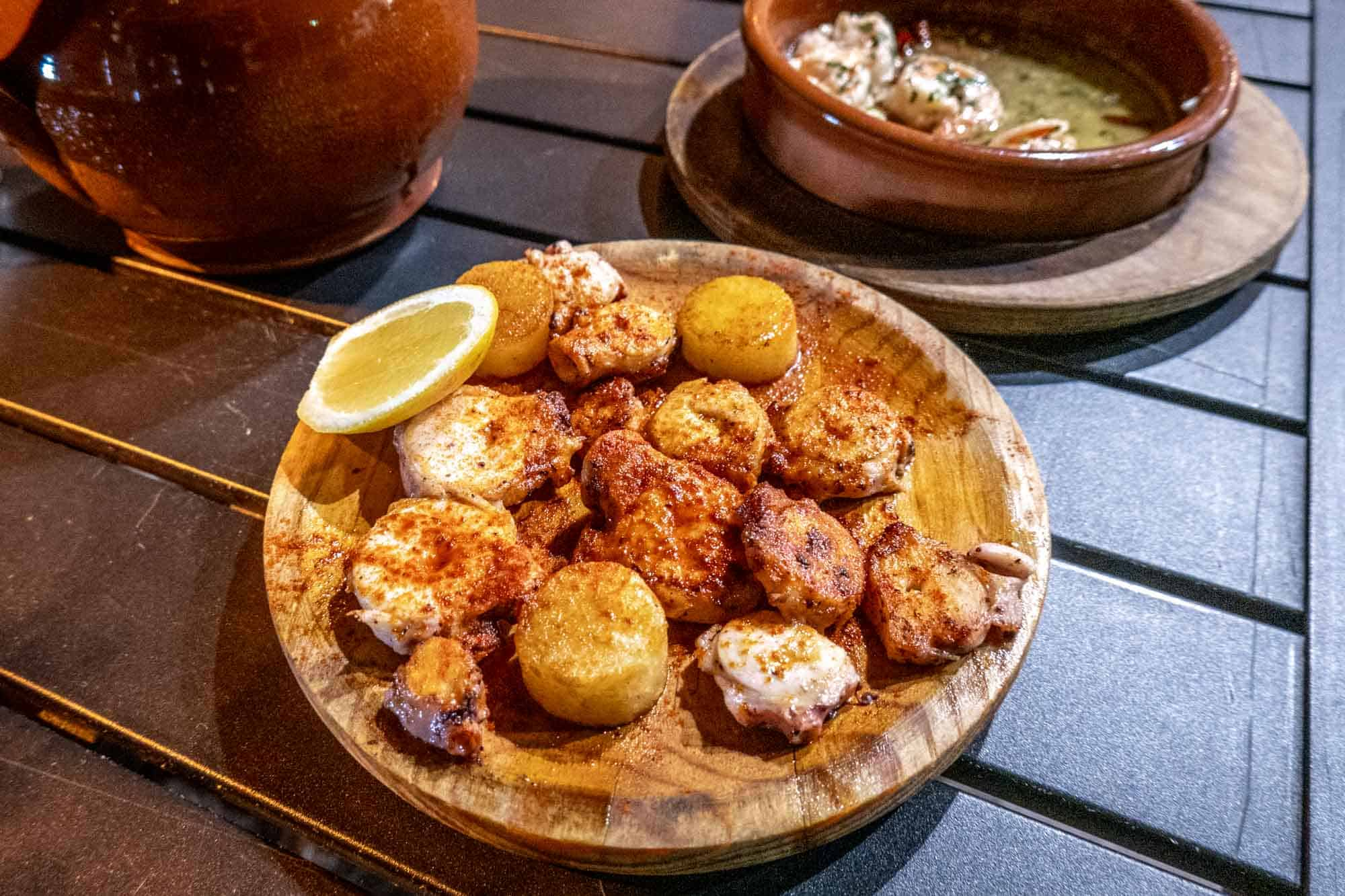 Medallions of octopus and potato on wood plate